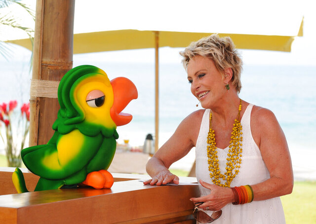 In this photo released on Nov. 2, 2020 by Globo, Globo TV presenter Ana Maria Braga smiles next to the parrot puppet Louro Jose, played by Tom Veiga, in Rio de Janeiro, Brazil. An outpouring of emotion in Brazil has followed news that the puppeteer behind Louro José, a two-foot-tall parrot that's a fixture on the country's most popular morning show, had passed away. (Globo via AP)