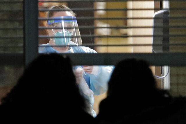 FILE - In this March 10, 2020, file photo, a worker wearing protective gear is seen through a window as she works in a room of a woman who has tested positive for the new coronavirus, as her daughters look in from outside the window, at the Life Care Center in Kirkland, Wash., near Seattle. Burgeoning coronavirus outbreaks at this and other nursing homes in Illinois, New Jersey and elsewhere are laying bare the risks of the industry's long-running problems, including a struggle to control infections and a staffing crisis that relies on poorly paid aides who can't afford to stay home sick.  (AP Photo/Ted S. Warren, File)