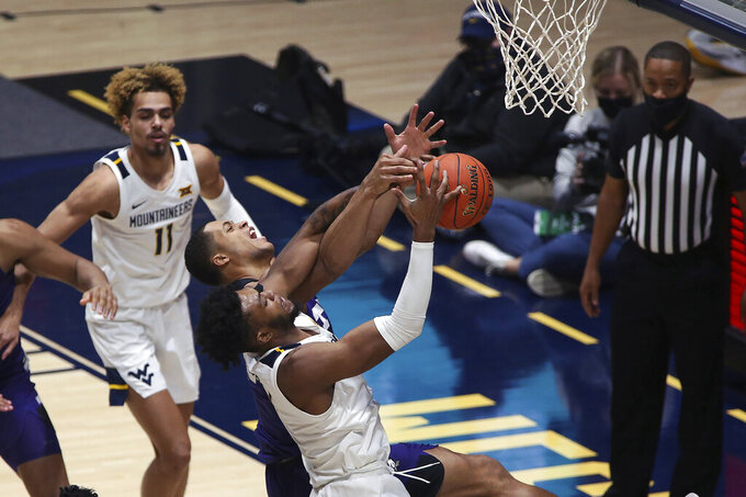 West Virginia forward Derek Culver (1) shoots while defended by Texas Christian forward Jaedon LeDee (23) during the second half of an NCAA college basketball game Thursday, March 4, 2021, in Morgantown, W.Va. (AP Photo/Kathleen Batten)