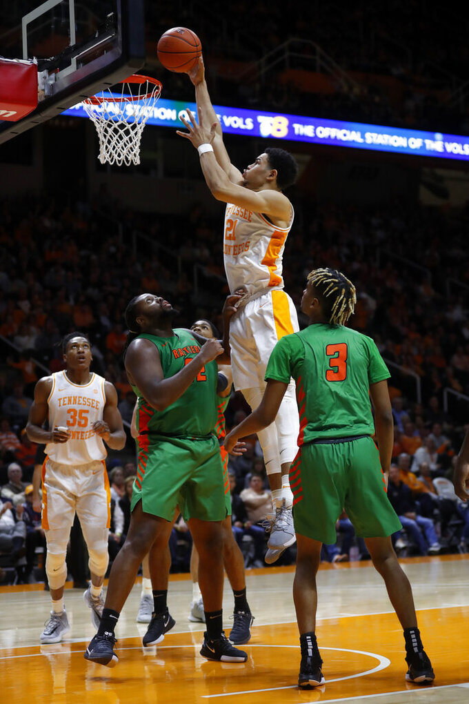 Tennessee forward Olivier Nkamhoua (21) dunks over Florida A&M center Evins Desir (22) during the first half of an NCAA college basketball game Wednesday, Dec. 4, 2019, in Knoxville, Tenn. (AP Photo/Wade Payne)