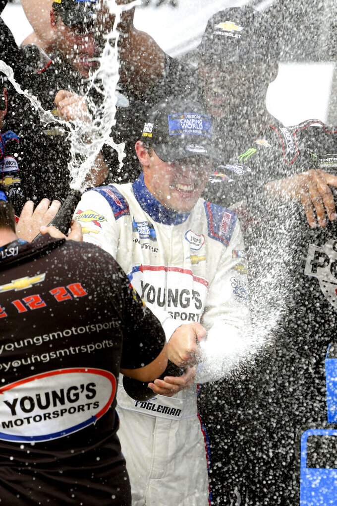 Tate Fogleman sprays a bottle in Victory Lane after winning a NASCAR Truck Series auto race Saturday, Oct. 2, 2021, in Talladega, Ala. (AP Photo/John Amis)