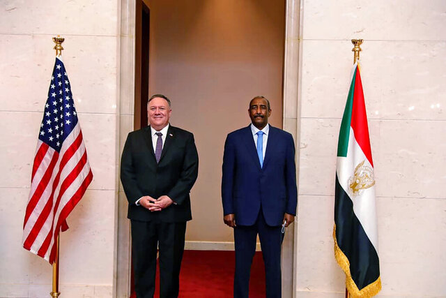 FILE - In this Aug. 25, 2020 file photo, U.S. Secretary of State Mike Pompeo stands with Sudanese Gen. Abdel-Fattah Burhan, the head of the ruling sovereign council, in Khartoum, Sudan. Officials in Sudan confirmed that a senior U.S.-Israeli delegation flew to Sudan on a private jet Wednesday, Oct. 21, 2020, and met with Burhan and others to wrap up a deal that would make Sudan the third Arab country to normalize ties with Israel this year. (Sudanese Cabinet via AP, File)