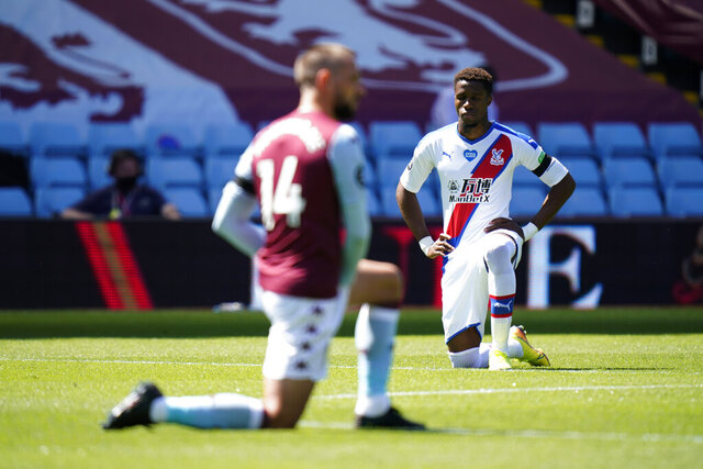 Crystal Palace's Wilfried Zaha takes a knee in support of the Black Lives Matter movement before the English Premier League soccer match between Aston Villa and Crystal Palace at Villa Park in Birmingham, England, Sunday, July 12, 2020. (Tim Keeton/Pool Photo via AP)