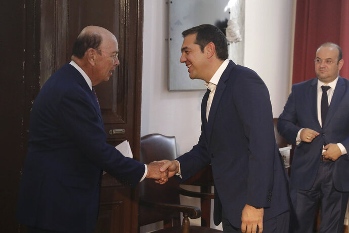Greek Prime Minister Alexis Tsipras, center, welcomes U.S. Commerce Secretary Wilbur Ross, left, during their meeting in the northern port city of Thessaloniki , Greece, on Friday, Sept 7, 2018.Thousands of police officers took up positions Friday around Greece's second-largest city ahead of anti-austerity protests at a trade fair where Tsipras met senior U.S. officials and is set to outline his post-bailout economic policy platform. (AP Photo/Dimitris Tosidis)