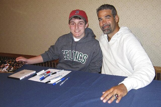 In this 2011 photo provided by David Cotillo, his son Chris Cotillo, left, poses with former Boston Red Sox third baseman Mike Lowell during an autograph session in Boston. Chris Cotillo, a Red Sox beat writer for MassLive.com in 2020, raised tens of thousands of dollars by selling autographed baseball memorabilia he had collected as a teen and that others donated for the auction. (David Cotillo via AP)