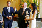 Meghan, right, Duchess of Sussex, reacts as she and Prince Harry, left, receive gifts from Australia's Governor General Sir Peter Cosgrove in Sydney, Australia, Tuesday, Oct. 16, 2018. Prince Harry and his wife Meghan are on a 16-day tour of Australia and the South Pacific.(Phil Noble/Pool via AP)
