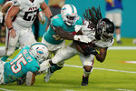 Atlanta Falcons running back D'Onta Foreman (38) is tackled by Miami Dolphins linebackers Jaelan Phillips (15) and Sam Eguavoen (49) during the second half of a NFL preseason football game, Saturday, Aug. 21, 2021, in Miami Gardens, Fla. (AP Photo/Wilfredo Lee)