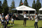 Stephen Curry shoots a basketball from the 17th green of the Silverado Resort North Course as Phil Mickelson watches during the pro-am for the Safeway Open PGA golf tournament Wednesday, Sept. 25, 2019, in Napa, Calif. (AP Photo/Eric Risberg)