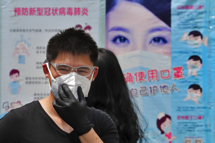 A man wearing groves adjusts his protective face mask as he walks by posters showing a proper way to wear a face mask to help curb the spread of the coronavirus in Beijing, Sunday, June 28, 2020. China has extended COVID-19 tests to newly reopened salons amid a drop in cases while South Korea continues to face new infections as it eases social distancing rules. (AP Photo/Andy Wong)