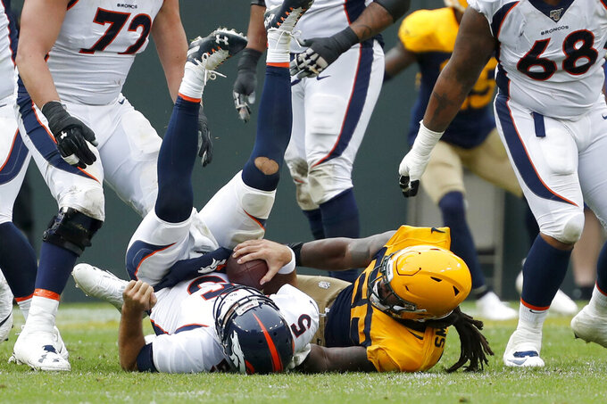 Denver Broncos quarterback Joe Flacco, left, is sacked by Green Bay Packers outside linebacker Za'Darius Smith during the first half of an NFL football game Sunday, Sept. 22, 2019, in Green Bay, Wis. (AP Photo/Matt Ludtke)