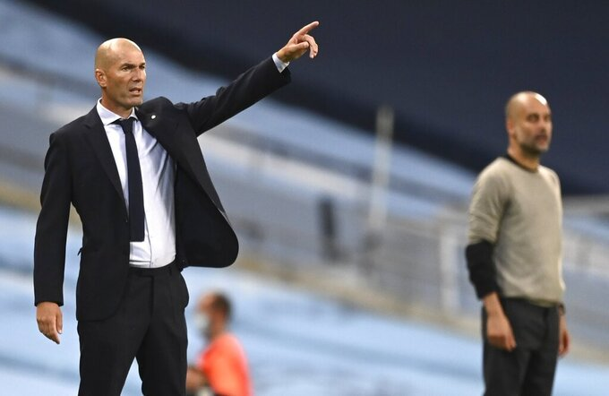 Real Madrid's head coach Zinedine Zidane, left, gestures as he stands alongside Manchester City's head coach Pep Guardiola during the Champions League round of 16, second leg soccer match between Manchester City and Real Madrid at the Etihad Stadium in Manchester, England, Friday, Aug. 7, 2020. (AP Photo/Shaun Botterill, Pool)