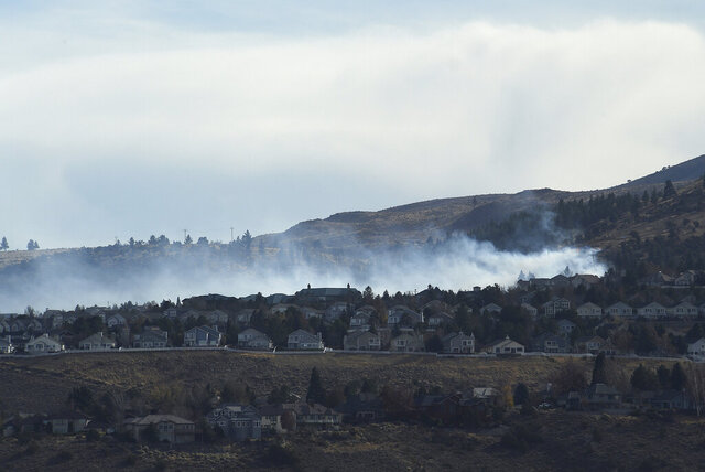 A fire is seen burning in the Caughlin Ranch area of Reno, Nev., on Tuesday, Nov. 17, 2020. Firefighters are battling a wildfire in southwest Reno that is threatening some homes in dangerously high winds. Dozens of residences were being evacuated on the edge of the Sierra foothills. (Jason Bean/The Reno Gazette-Journal via AP)