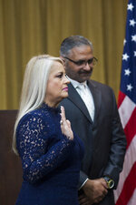 Justice Secretary Wanda Vazquez is sworn in as governor, accompanied by her husband Judge Jorge Diaz, in San Juan, Puerto Rico, Wednesday, Aug. 7, 2019. Vazquez took the oath of office early Wednesday evening at the Puerto Rican Supreme Court, which earlier in the day ruled that Pedro Pierluisi's swearing in last week was unconstitutional. (AP Photo/Dennis M. Rivera Pichardo)