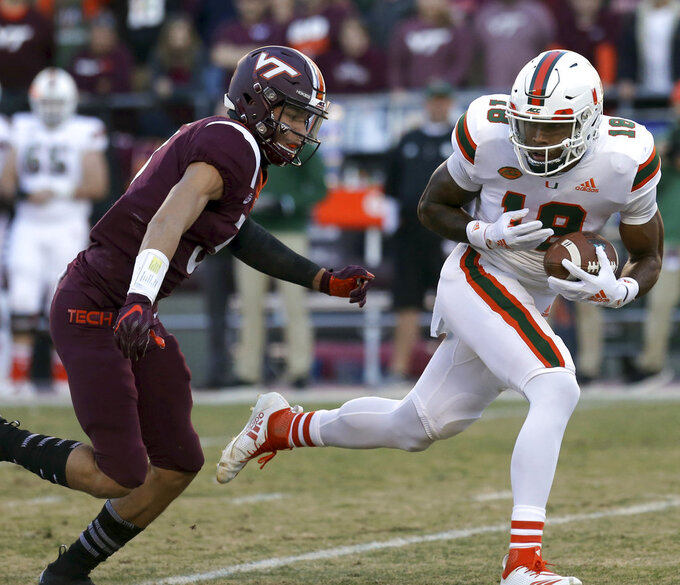 Miami receiver Lawrence Cager (18) escapes Virginia Tech defender Caleb Farley (3) in the first half of an NCAA college football game in Blacksburg, Va., Saturday, Nov. 17 2018. (Matt Gentry/The Roanoke Times via AP)