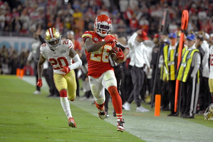 CORRECTS THE WINNING TOUCHDOWN TO THE FINAL TOUCHDOWN - Kansas City Chiefs' Damien Williams, right, runs away from San Francisco 49ers' Jimmie Ward on his way to the final touchdown during the second half of the NFL Super Bowl 54 football game Sunday, Feb. 2, 2020, in Miami Gardens, Fla. (AP Photo/Mark J. Terrill)