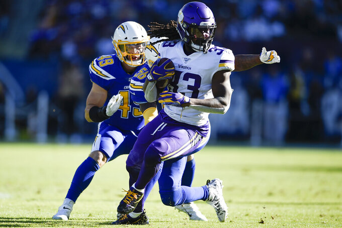 FILE - In this Sunday, Dec. 15, 2019, file photo, Minnesota Vikings running back Dalvin Cook runs with the ball during the first half of an NFL football game against the Los Angeles Chargers in Carson, Calif. The Vikings are expecting Cook to report on time for training camp, coach Mike Zimmer said Saturday, July 25, 2020. Cook has begun the final year of his rookie contract and took a break from the virtual offseason program in June, seeking a new deal. (AP Photo/Kelvin Kuo, File)