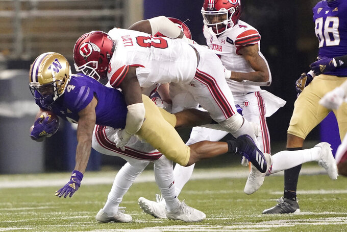 Washington wide receiver Terrell Bynum is tackled by Utah linebacker Devin Lloyd (0) during the second half of an NCAA college football game Saturday, Nov. 28, 2020, in Seattle. Washington won 24-21. (AP Photo/Ted S. Warren)