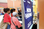 FILE - In this Oct. 1, 2019, file photo people wait in line to inquire about job openings with Marshalls during a job fair at Dolphin Mall in Miami. On Friday, Dec. 6, the U.S. government issues the November jobs report. (AP Photo/Lynne Sladky, File)