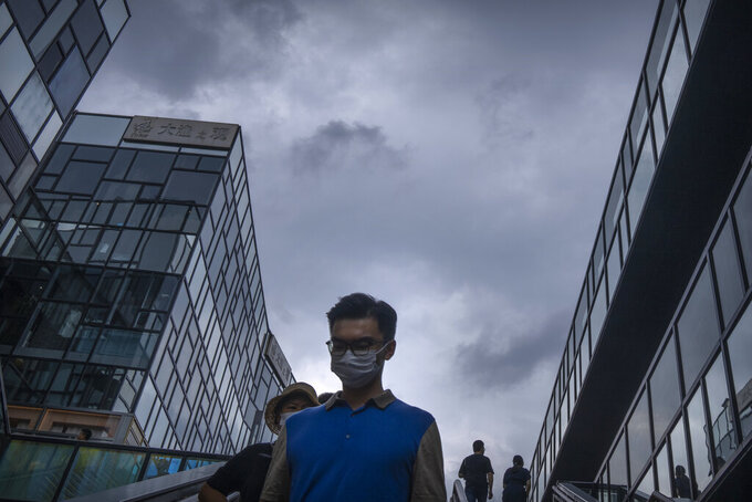 People wearing face masks to prevent the spread of COVID-19 walk at a shopping mall in Beijing, Saturday, July 17, 2021. A senior Chinese health official says China cannot accept the World Health Organization's plan for the second phase of a study into the origins of COVID-19. (AP Photo/Mark Schiefelbein)