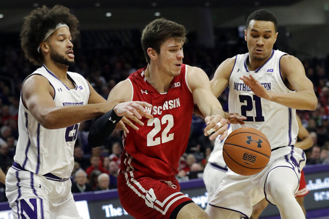 Wisconsin forward Ethan Happ (22) battles for the ball against Northwestern center Barret Benson, left, and forward A.J. Turner during the first half of an NCAA college basketball game Saturday, Feb. 23, 2019, in Evanston, Ill. (AP Photo/Nam Y. Huh)
