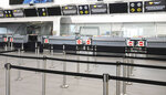 General view of the deserted Thomas Cook check-in counters at Birmingham airport in Birmingham, England, Monday, Sept. 23, 2019.  Hundreds of thousands of travellers were stranded across the world Monday after British tour company Thomas Cook collapsed early Monday, immediately halting almost all its flights and hotel services and throwing employees out of work. (AP Photo/Rui Vieira)
