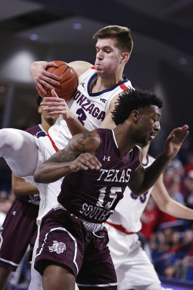 Gonzaga forward Filip Petrusev, left, grabs a rebound over Texas Southern forward Justin Hopkins during the first half of an NCAA college basketball game in Spokane, Wash., Wednesday, Dec. 4, 2019. (AP Photo/Young Kwak)