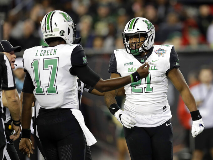 Marshall running back Anthony Anderson (21) celebrates with quarterback Isaiah Green (17) after Anderson scored a 1-yard touchdown against South Florida during the first half of the Gasparilla Bowl NCAA college football game Thursday, Dec. 20, 2018, in Tampa, Fla. (AP Photo/Chris O'Meara)
