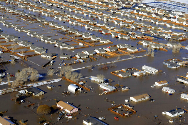 FILE - In this Jan. 5, 2008, file photo, the Truckee Carson Irrigation Ditch gave way causing much of Fernley, Nev., to be flooded. A political storm is brewing on northern Nevada's high desert that locals say could prove as devastating as the rare heavy rainfall that preceded the failure of a poorly maintained, century-old earthen irrigation canal and flooded hundreds of homes in 2008. (Marilyn Newton/The Reno Gazette-Journal via AP, File)