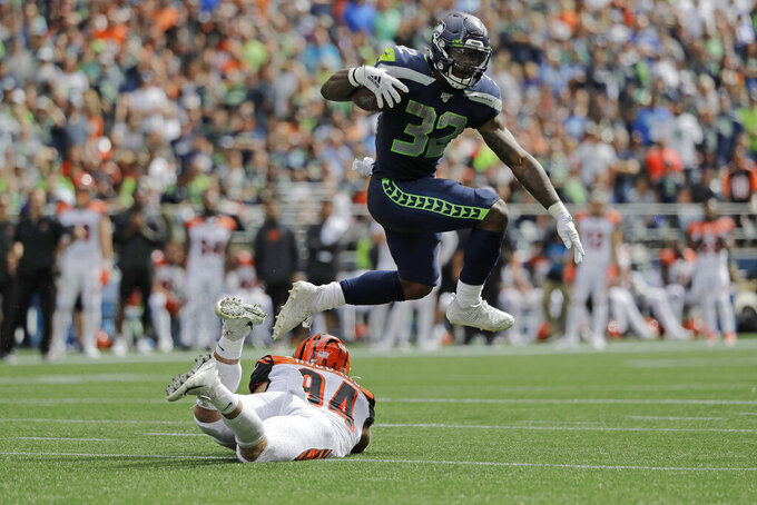 Seattle Seahawks running back Chris Carson leaps over Cincinnati Bengals defensive end Sam Hubbard as he carries the ball during the first half of an NFL football game, Sunday, Sept. 8, 2019, in Seattle. (AP Photo/John Froschauer)