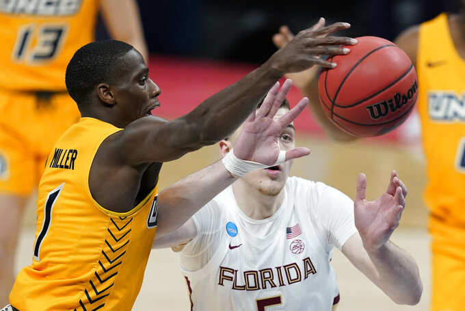 UNC-Greensboro's Isaiah Miller (1) and Florida State's Balsa Koprivica (5) battle for a loose ball during the first half of a first-round game in the NCAA men's college basketball tournament at Banker's Life Fieldhouse, Saturday, March 20, 2021, in Indianapolis. (AP Photo/Darron Cummings)