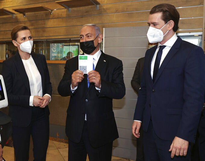 """Israeli Prime Minister Benjamin Netanyahu, center, holds a """"Green Pass,"""" for citizens vaccinated against COVID-19,  as he visits a fitness gym with Austrian Chancellor Sebastian Kurz, right, and Danish Prime Minister Mette Frederiksen, to observe how the pass is used, in Modi'in, Israel, Thursday, March 4, 2021. Frederiksen and Kurz are on a short visit to Israel for to pursue the possibilities for closer cooperation on COVID-19 and vaccines. (Avigail Uzi/Pool via AP)"""