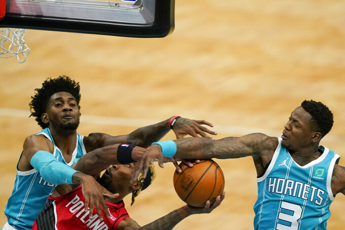 Portland Trail Blazers forward Rondae Hollis-Jefferson drives to the basket between Charlotte Hornets forward Jalen McDaniels and guard Terry Rozier (3) during the first half in an NBA basketball game on Sunday, April 18, 2021, in Charlotte, N.C. (AP Photo/Chris Carlson)