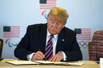 President Donald Trump signs a document pledging the support of the federal government during a briefing with the U.S. Olympic and Paralympic Committee and Los Angeles 2028 organizers, Tuesday, Feb. 18, 2020, in Beverly Hills, Calif. (AP Photo/Evan Vucci)