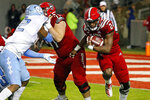 North Carolina State's Zonovan Knight (24) rushes the ball past a battle between North Carolina State's Joe Sculthorpe (71) and North Carolina's Tomon Fox (12) during the first half of an NCAA college football game in Raleigh, N.C., Saturday, Nov. 30, 2019. (AP Photo/Karl B DeBlaker)
