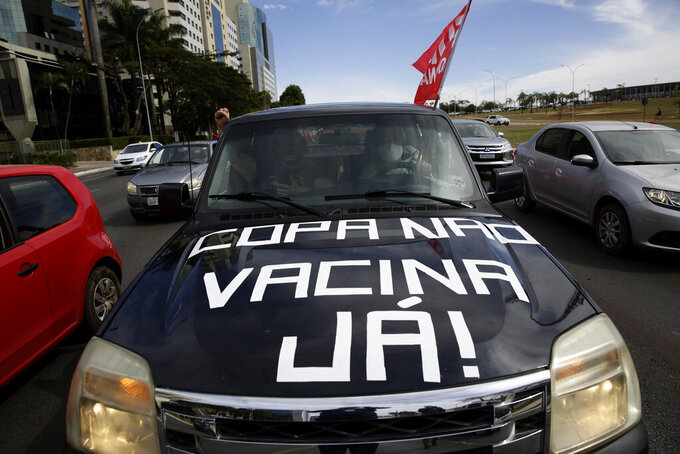 """Protesters drive their car with a sign reading in Portuguese """"Copa No, Vaccines Now"""" to protest the holding of Copa America in Brasilia, Brazil, Sunday, June 6, 2021. Brazil accepted hosting the South American soccer tournament after the original co-hosts were dropped: Colombia due to political protests and Argentina for rising of COVID-19 cases. (AP Photo/Eraldo Peres)"""