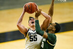 FILE - Iowa center Luka Garza (55) drives to the basket against Michigan State forward Marcus Bingham Jr., right, during the second half of an NCAA college basketball game in Iowa City, Iowa, in this Tuesday, Feb. 2, 2021, file photo. Garza has made The Associated Press All-America first team, announced Tuesday, March 16, 2021.(AP Photo/Charlie Neibergall, File)