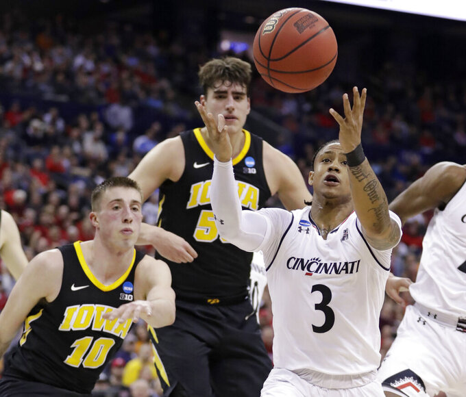 Cincinnati's Justin Jenifer (3) grabs a rebound ahead of Iowa's Joe Wieskamp (10) in the first half during a first round men's college basketball game in the NCAA Tournament in Columbus, Ohio, Friday, March 22, 2019. (AP Photo/Tony Dejak)