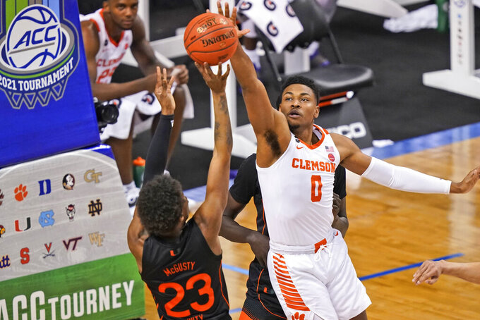 Clemson guard Clyde Trapp (0) blocks the shot of Miami guard Kameron McGusty (23) during the first half of an NCAA college basketball game in the second round of the Atlantic Coast Conference tournament in Greensboro, N.C., Wednesday, March 10, 2021. (AP Photo/Gerry Broome)