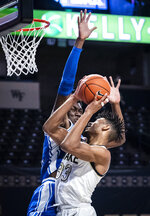 Wake Forest forward Ody Oguama (33) shoots as he is fouled by Duke center Mark Williams duirng an NCAA college basketball game Wednesday, Feb. 17, 2021, in Wintson-Salem, N.C. (Andrew Dye/The Winston-Salem Journal via AP, Pool)