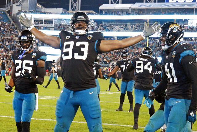 FILE - In this Sunday, Dec. 29, 2019, file photo, Jacksonville Jaguars defensive end Calais Campbell (93) celebrates his touchdown against the Indianapolis Colts on a fumble recovery with safety Jarrod Wilson (26) and linebacker Josh Allen (41) during the second half of an NFL football game, in Jacksonville, Fla. On Sunday, March 15, 2020, the Baltimore Ravens agreed to trade a fifth-round draft pick in the upcoming draft to the Jacksonville Jaguars for veteran defensive lineman Calais Campbell. (AP Photo/Stephen B. Morton, File)