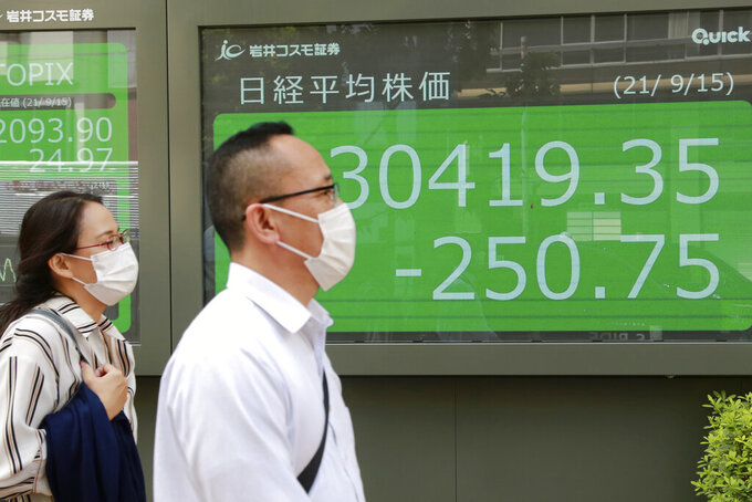 People walk by an electronic stock board of a securities firm in Tokyo, Wednesday, Sept. 15, 2021. Asian stock markets followed Wall Street down on Wednesday after U.S. inflation was lower than expected amid unease about the impact of the spread of the coronavirus's delta variant. (AP Photo/Koji Sasahara)