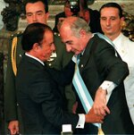 FILE - In this Dec. 10, 1999, file photo, Fernando De la Rua, right, receives the presidential sash from outgoing president Carlos Menem after he was sworn in as Argentina's 47th president during a inaugural ceremony at Buenos Aires' Government House. Former Argentine President Fernando De la Rúa, who attracted voters with his image as an honest statesman and later left the country plunged into its worst economic crisis, died Tuesday, July 9, 2019. He was 81.(AP Photo/Gerardo Horovitz, File)