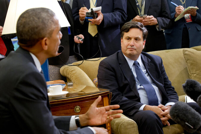 FILE- In this Oct. 22, 2014, file photo, reporters take notes as Ebola coordinator Ron Klain listens to President Barack Obama speak to the media about the government's Ebola response in the Oval Office of the White House in Washington. New federal Ebola response squads are being readied to rus to an U.S. city where a new Ebola case might be identified, officials said. Klain is preparing to serve as President-elect Joe Biden's chief of staff, a job often referred to as the nation's chief operating officer. (AP Photo/Jacquelyn Martin, File)