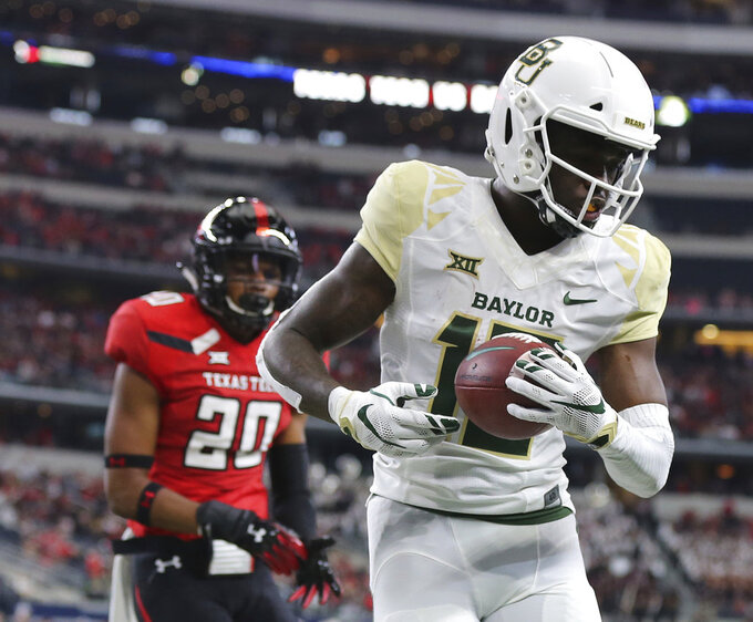 Baylor wide receiver Denzel Mims (15) catches a touchdown pass against Texas Tech defensive back Adrian Frye (20) in the first half of an NCAA college football game Saturday, Nov. 24, 201 in Arlington, Texas. (Jerry Larson/Waco Tribune-Herald via AP)