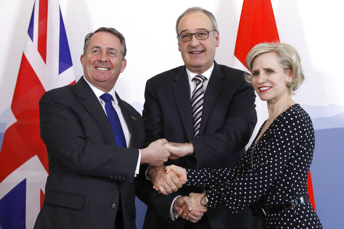 Swiss Federal Councillor Guy Parmelin, center, British Secretary of State for International Trade Liam Fox, left, and Liechtenstein's Foreign Minister Aurelia Frick, right, shake hands after signing a trade agreement in Bern, Switzerland, Monday, Feb. 11, 2019. Parmelin and Fox signed a bilateral trade agreement regulating relations between the two countries after the Brexit. Because of the customs treaty with Switzerland, the agreement also applies to Liechtenstein. (Peter Klaunzer/Keystone via AP)