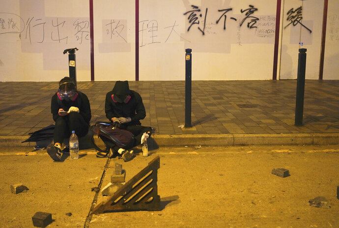 Protestors rest near a road barricaded with bricks in Hong Kong, early Tuesday, Nov. 19, 2019. About 100 anti-government protesters remained holed up at a Hong Kong university Tuesday as a police siege of the campus entered its third day. (AP Photo/Vincent Yu)