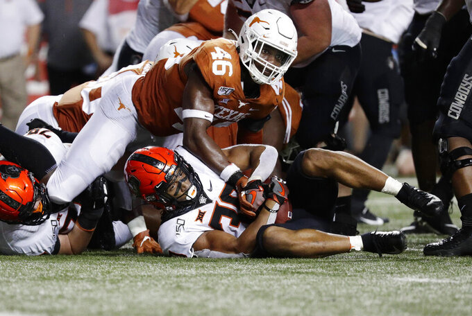 Oklahoma State running back Chuba Hubbard (30) is stopped short of a first down by Texas linebacker Joseph Ossai (46) on fourth down near the goal line during the second half of an NCAA college football game Saturday, Sept. 21, 2019, in Austin, Texas. (AP Photo/Eric Gay)