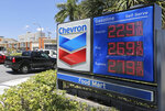 FILE - In this May 15, 2017, file photo, motorists pass a Chevron sign listing gas prices, in Miami Springs, Fla.  On Thrusday, Oct. 29, 2020, Chevron plans to cut a quarter of the employees at Noble Energy as the pandemic saps demand for fuel.  (AP Photo/Alan Diaz, File)