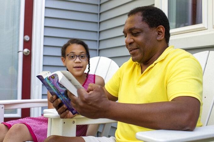 """Andrew Grant-Thomas reads to his daughter, Lena Grant-Giraud, on the back porch at their home in Amherst, Mass., on Monday, May 24, 2021. Grant-Thomas and his wife, Melissa Giraud, started the nonprofit EmbraceRace in 2016 when they found few resources to help them talk with their young daughters about race. The nonprofit's approach, Grant-Thomas says, can be summed up in a simple mantra: """"Start young, and keep going."""" (M. Scott Brauer/Chronicle of Philanthropy via AP)"""