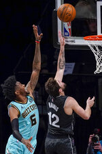 Brooklyn Nets forward Joe Harris (12) goes to the basket past Charlotte Hornets forward Jalen McDaniels (6) during the second half of an NBA basketball game Friday, April 16, 2021, in New York. (AP Photo/Mary Altaffer)